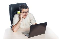 Man looking at laptop and shouting. Man sitting at the table looking at laptop and shouting at the mobile phone Stock Photos