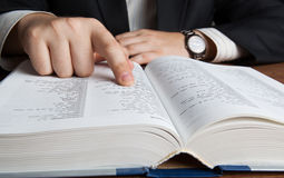 Man looking in the large dictionary. Close up royalty free stock photo