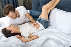 Man looking at laughing woman while lying in bed stock image
