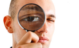 Man looking through a lens Royalty Free Stock Image