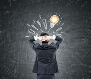 Man looking at light bulb, exclamation marks Stock Image