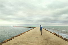 Man looking at the lighthouse in seascape Royalty Free Stock Images