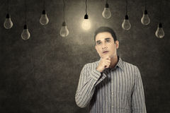 Man looking at lit lightbulb Royalty Free Stock Photography