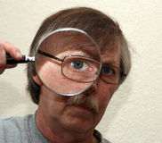 Man looking through magnifier Royalty Free Stock Photos