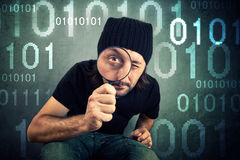Man looking through magnifying glass. And inspecting binary code Royalty Free Stock Photos