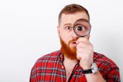 Man looking at magnifying glass stock photos