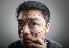 Man looking through a magnifying glass Royalty Free Stock Image