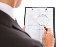 Man looking through magnifying glass on clipboard Stock Photography