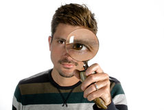Man looking through magnifying glass. A man looking through a magnifying glass with an eye enlarged Royalty Free Stock Photography