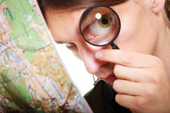 Man looking through a magnifying glass at map Stock Photos