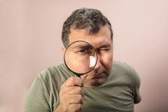 Man looking through magnifying glass. Middle aged man in t-shirt looking through magnifying glass at camera, what makes his eye seem bigger Stock Image
