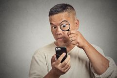 Man looking through magnifying glass on smart phone Stock Photos