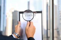 Man looking through a  magnifying glass  to the Blank of contract Stock Images