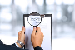 Man looking through a  magnifying glass  to the Blank of contract Stock Photography