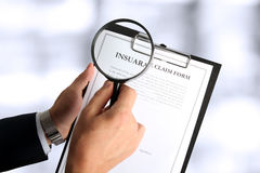 Man looking through a  magnifying glass  to the Blank insurance claim form Royalty Free Stock Photography