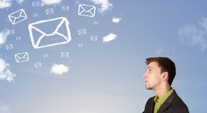 Man looking at mail symbol clouds on blue sky Stock Images