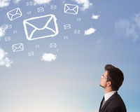 Man looking at mail symbol clouds on blue sky Royalty Free Stock Image