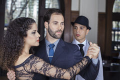 Man Looking At Male And Female Tango Dancers Performing Together. Young men looking at male and female tango dancers performing together in restaurant Stock Photography