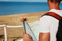 Man looking at map infront of sea, active summer holiday vacation Stock Image