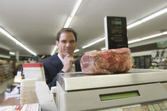 Man Looking At Meat On Weighing Machine Stock Photography
