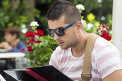 man looking at the menu and deciding what to order. Royalty Free Stock Image