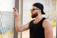 Man looking through metal urban fence wearing sunglasses and cap. Close up portrait of young bearded man looking through metal urban fence wearing sunglasses and Stock Photography
