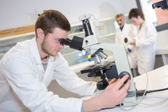 Man looking through microscope Royalty Free Stock Photos