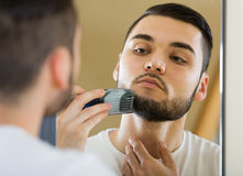 Man looking at mirror and shaving beard with trimmer Stock Photography