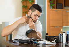 Man looking at mirror and shaving beard with trimmer Royalty Free Stock Photos