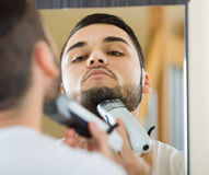 Man looking at mirror and shaving beard with trimmer Royalty Free Stock Photo