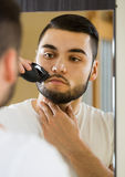 Man looking at mirror and shaving beard with trimmer Stock Photos
