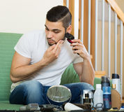 Man looking at mirror and shaving beard with trimmer Royalty Free Stock Image