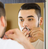 Man looking at mirror and shaving face with razor Stock Image