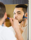 Man looking at mirror and shaving face with razor Royalty Free Stock Image