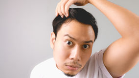 A man looking at the mirror and shocked that he is losing his ha. Ir. An asian man with white t-shirt and grey background stock photography