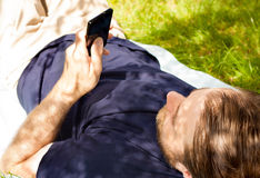 Man looking at mobile phone while laying on grass Stock Photo