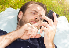 Man looking at mobile phone while laying on grass Royalty Free Stock Photos