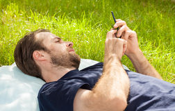 Man looking at mobile phone while laying on grass Stock Image
