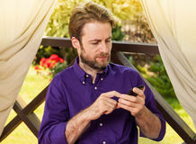 Man looking at mobile phone outdoor on garden terrace Stock Images