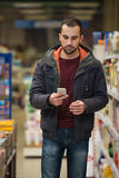 Man Looking At Mobile Phone In Shopping Centre Royalty Free Stock Photo