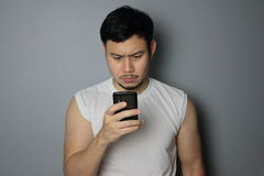 A man is looking on the mobile phone. A man is thinking after he got a message royalty free stock image
