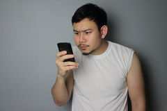 A man is looking on the mobile phone. A man is thinking after he got a message royalty free stock photography