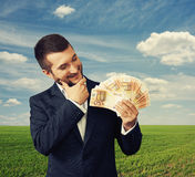 Man looking at money and thinking Stock Images
