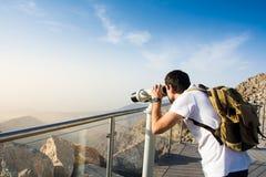 Man using public binoculars at the mountain top. Man looking at the mountain range view from public binoculars stock image