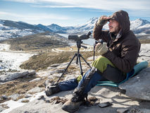 Man looking in the mountains with binoculars and telescope Stock Photos