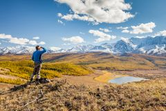 A Man looking at the Mountains and a Lake below from Viewpoint. stock photography