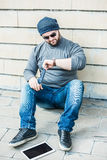 Man looking nervously at his watch with a tablet. Man dressed with jeans, grey top, sneakers and a hat, sitting on the floor Royalty Free Stock Images