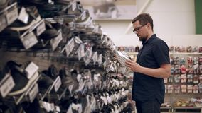 Shopping for sneakers. Man looking for a new daily sneakers in a supermarket. Man standing in a shoe aisle and choosing shoes. Guy wants to buy new kicks. Large stock video footage
