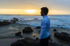 Man Looking Ocean Horizon Rocks Silhouetted. Young man dressed white shirt black longs looking out to horizon silhouetted on beach ocean rocks at dawn sunrise Royalty Free Stock Image