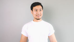 A man looking out as he found someone or something. An asian man with white t-shirt and grey background royalty free stock photo